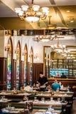 Европейский интерьер бистро с сервировками стола и цветным стеклом люстр Стоковые Изображения