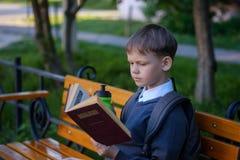 Европейский мальчик ест завтрак школы на скамейке в парке Стоковое фото RF