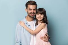 Европейский отец возникновения и маленькая съемка студии обнимать дочери стоковое фото
