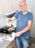 Европейский парень льет кофе в бак чашки кофе Стоковые Фото