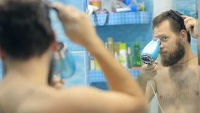 Европейский человек высушивать волосы и борода в ванной комнате перед зеркалом видеоматериал