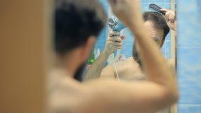 Европейский человек высушивать волосы и борода в ванной комнате перед зеркалом акции видеоматериалы