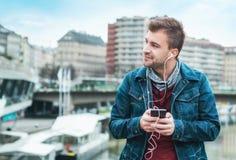 Европейский человек имеет время потехи Музыкальный образ жизни Жизнерадостный стильный парень с музыкой smartphone слушая Стоковая Фотография