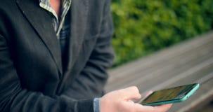 Европейский человек используя смартфон в парке сток-видео