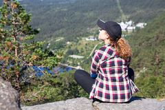 Европейский hiker женщины нося в рубашке и крышке шотландки сидит на крае скалы в горах, космоса экземпляра стоковое изображение