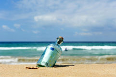 евро 100 в бутылке на береге океана Стоковые Фотографии RF