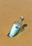 100 евро в бутылке на песке пляжа Стоковая Фотография