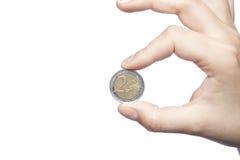 2 евро держат в пальцах, белой предпосылке, космосе экземпляра Стоковая Фотография