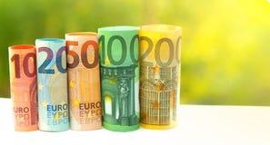 Евро 10, 20, 50, 100 и 200 свернуло банкноты счетов на запачканной зеленым цветом предпосылке bokeh Стоковое Изображение RF