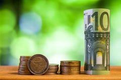 100 евро свернуло банкноту счета с монетками евро на деревянном Стоковые Фотографии RF