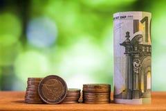 100 евро свернуло банкноту счета с монетками евро на деревянном Стоковая Фотография