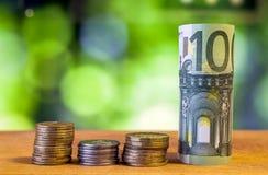 100 евро свернуло банкноту счета с монетками евро на деревянном Стоковые Фото