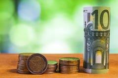 100 евро свернуло банкноту счета с монетками евро на деревянном Стоковое Изображение RF