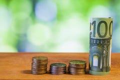 100 евро свернуло банкноту счета с монетками евро на деревянном Стоковое фото RF