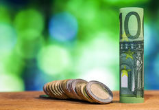 100 евро свернуло банкноту счета, с монетками евро на зеленом цвете Стоковые Фото