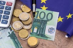 100 евро сорванных с монетками, ручкой и калькулятором Стоковое фото RF