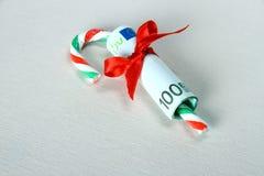 100 евро с красной тросточкой ленты и конфеты Стоковая Фотография