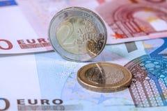 Евро чеканит на предпосылке банкнот евро, концепции дела Стоковые Изображения