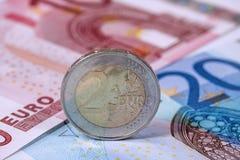 Евро чеканит на предпосылке банкнот евро, концепции дела Стоковое Изображение