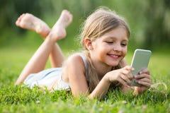 девушка ¿ ï» лежа в парке с мобильным телефоном Стоковое Фото