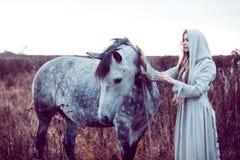 девушка в с капюшоном плаще с лошадью, влиянием тонизировать стоковое фото rf