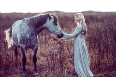 девушка в с капюшоном плаще с лошадью, влиянием тонизировать стоковое изображение rf