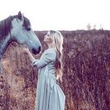 девушка в с капюшоном плаще с лошадью, влиянием тонизировать стоковые фото