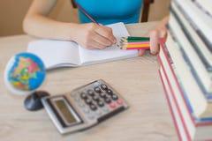 девушка делая уроки дома книги на столе в аудитории Изучать девушки Стоковое фото RF