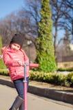 девушка имеет потеху на самокате в теплом весеннем дне Стоковое Изображение