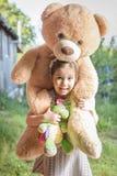девушка камеры медведя предпосылки осени красивейшая счастливая ее маленькие смотря валы игрушечного плеча сь желтеет Стоковое Изображение