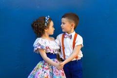 девушка мальчика вручает удерживание Valentine& x27; день s любовная история девушки сада мальчика целуя Стоковая Фотография