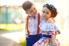 девушка мальчика вручает удерживание Valentine& x27; день s любовная история девушки сада мальчика целуя Стоковая Фотография RF