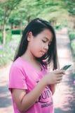 девушка меньший мобильный телефон используя Стоковые Изображения