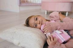 девушка обнимая подарочную коробку рождества усмехаясь ребенк лежа на подушке и держать настоящий момент Стоковое Изображение