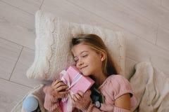 девушка обнимая подарочную коробку рождества усмехаясь ребенк лежа на подушке и держать настоящий момент Стоковые Изображения