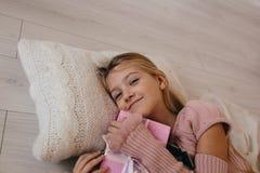 девушка обнимая подарочную коробку рождества усмехаясь ребенк лежа на подушке и держать настоящий момент Стоковое Изображение RF