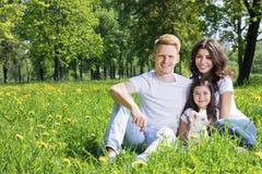 девушка отца семьи мальчика предпосылки обнимая его маленький супруга пруда парка мати человека Стоковые Изображения
