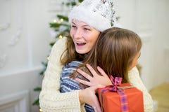2 девушка, подарок, рождественская елка, белые шляпы Стоковая Фотография RF