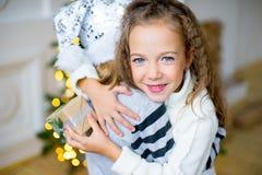 2 девушка, подарок, рождественская елка, белые шляпы Стоковые Фото