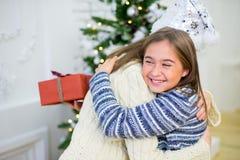 2 девушка, подарок, рождественская елка, белые шляпы Стоковая Фотография