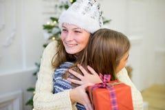 2 девушка, подарок, рождественская елка, белые шляпы Стоковые Фотографии RF