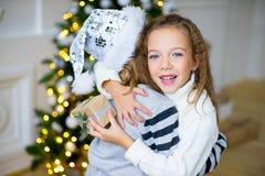 2 девушка, подарок, рождественская елка, белые шляпы Стоковое Изображение RF