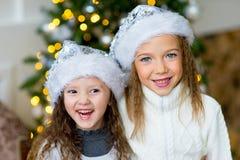 2 девушка, подарок, рождественская елка, белые шляпы Стоковое фото RF