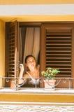 девушка смотрит вне окно стоковое фото