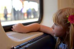 девушка смотря вне детенышей окна Стоковое Фото