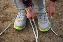 девушка совершает внешняя прогулка и остановленная для того чтобы связать его шнурки на тапках стоковое фото