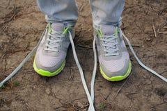 девушка совершает внешняя прогулка и остановленная для того чтобы связать его шнурки на тапках стоковое изображение