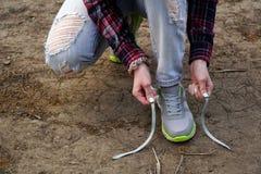 девушка совершает внешняя прогулка и остановленная для того чтобы связать его шнурки на тапках стоковое изображение rf