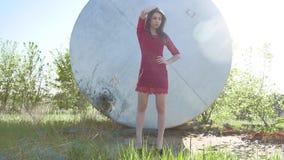 девушка строгая Серьезная девушка стоит около бочонка масла нефти Старое масло бочонка Стоковое Фото