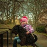 девушка с его черной собакой шнауцера на деревянной скамье Стоковое Изображение RF